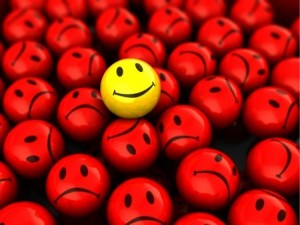 abstract 3d illustration of one yellow happy face over red unhappy crowd